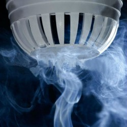 stock-photo-macro-view-of-wispy-smoke-around-white-fire-sensor-or-smoke-detector-dark-background-53917399